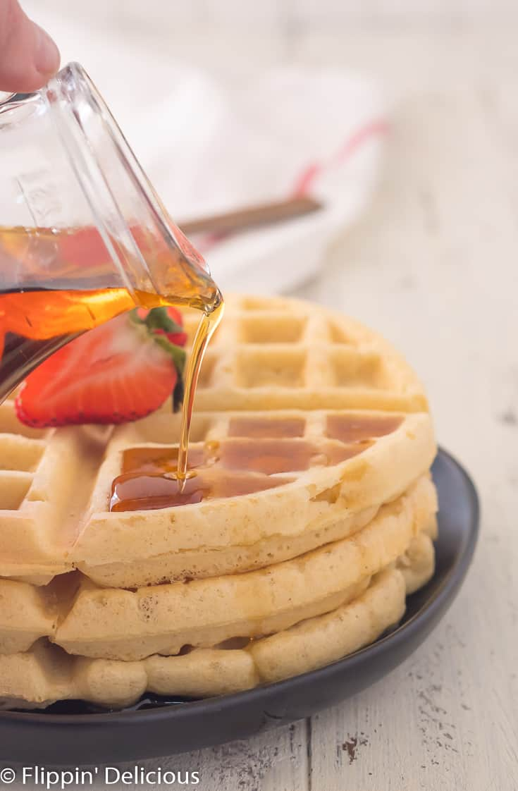 pouring maple syrup on stack of three gluten free Belgian waffles with sliced strawberry