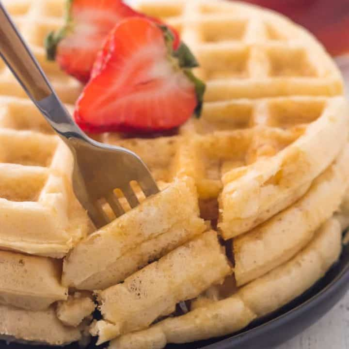 fork taking a bite out of stack of three gluten free waffles on plate with maple syrup and sliced strawberry