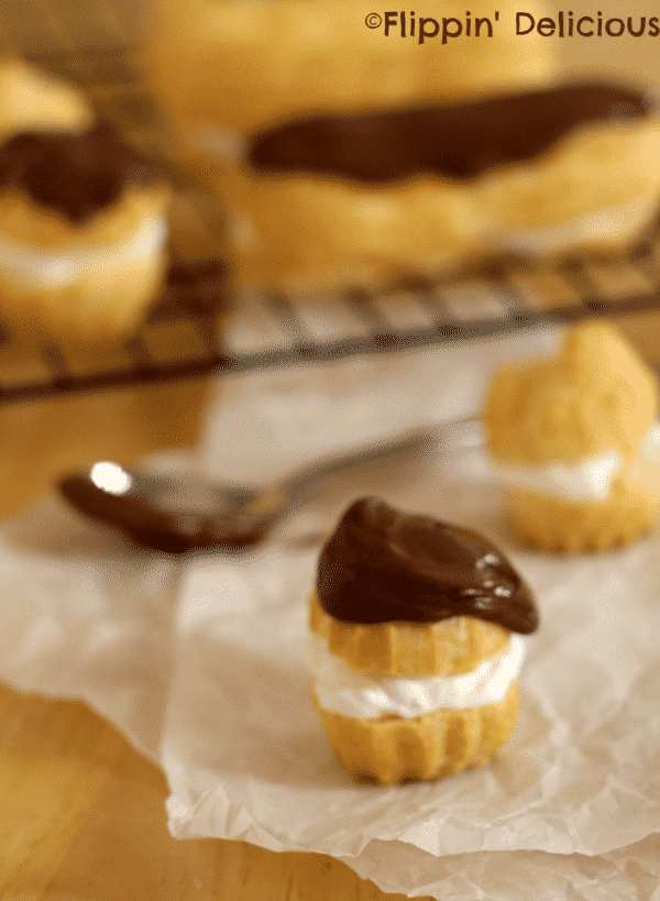 gluten free eclairs filled with cream and topped with chocolate ganache and salted caramel on a black cooling rack with a spoon and gluten free cream puffs in the foreground