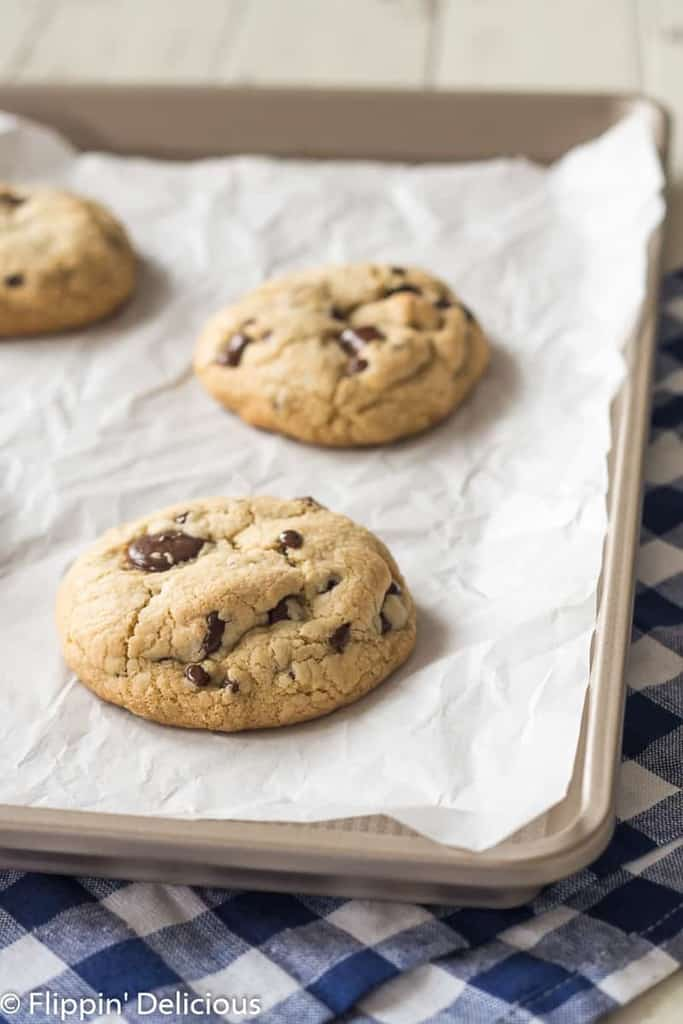three gluten free chocolate chip cookies with golden edges on a baking sheet lined with white parchment paper