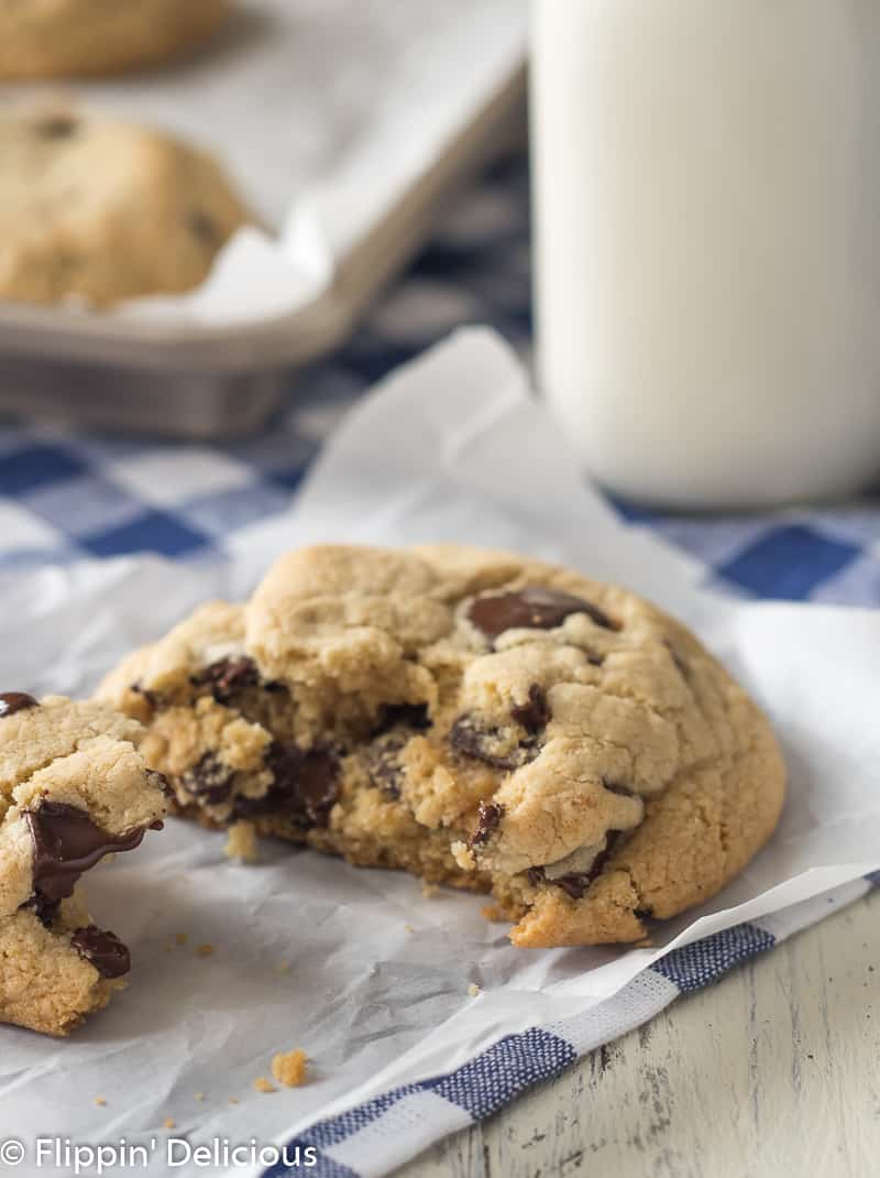 A moist gluten free chocolate chip cookie broken in half on a piece of white parchment paper on a blue checked napkin