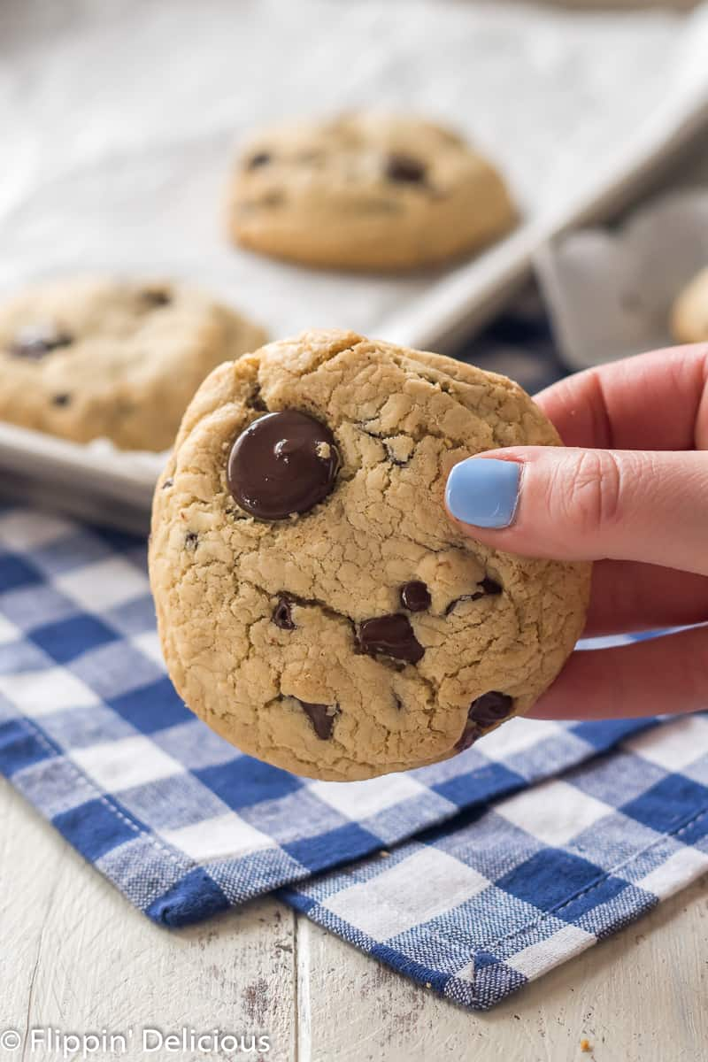 hand with blue nail polish holding a giant gluten free chocolate chip cookie with a blue checked napkin and a cookie sheet with more gluten free chocolate chip cookies in the background