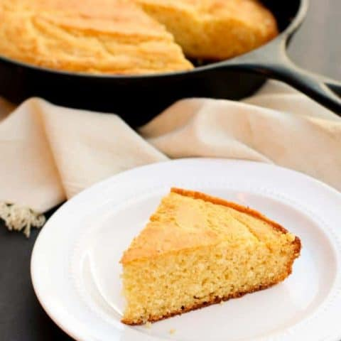 gluten free corn bread wedge on a white plate with skillet of gluten free honey cornbread in the background