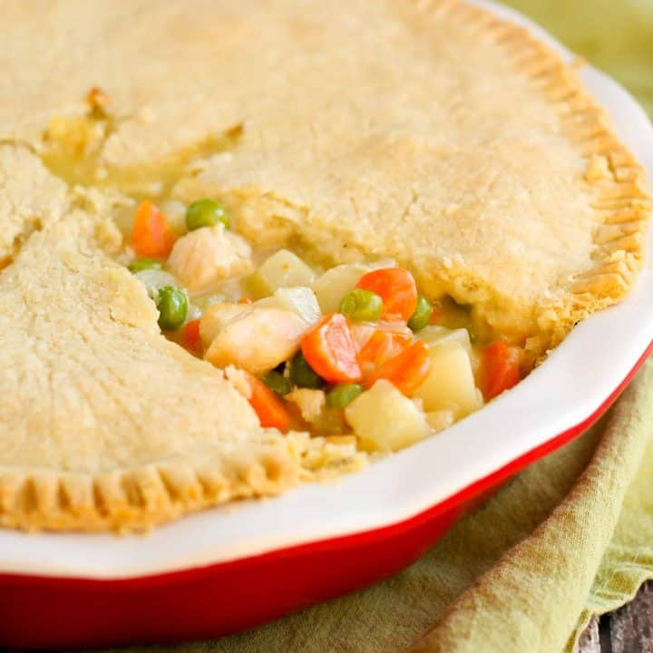 gluten free chicken pot pie in a red ceramic pie dish ith a slice of gluten free pie crust removed so you can see the chicken, potato, carrots, and celery