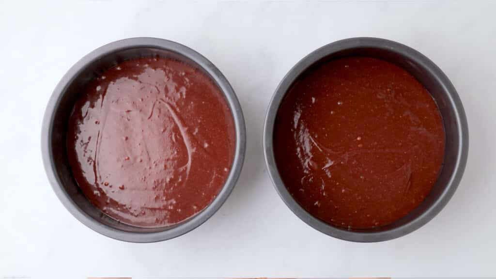 gluten free red velvet cake batter in metal pans on a white table ready to bake