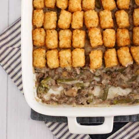 overhead gluten free tater tot casserole made with gluten free cream of mushroom soup in a white casserole dish with ground turkey