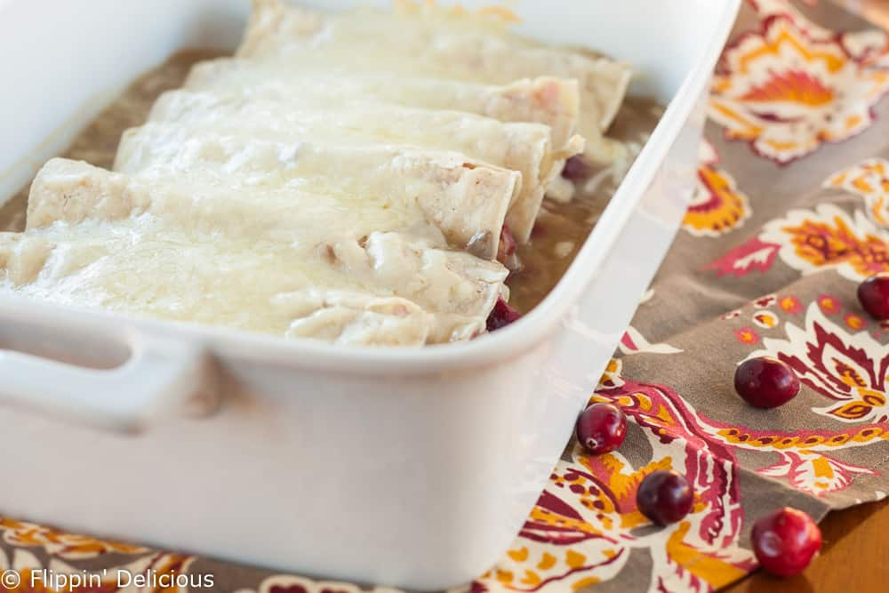 These Gluten Free Cranberry Turkey Enchiladas make the perfect day-after-Thanksgiving meal. Roasted turkey, creamy gravy, and fresh cranberry sauce rolled in warm corn tortillas and topped with gooey melted Monterrey Jack cheese.