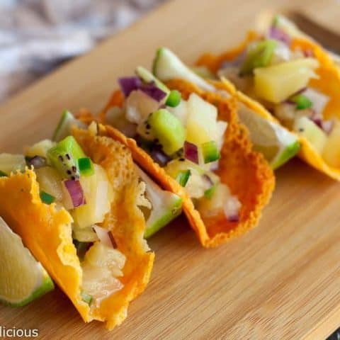 Crispy melted cheese forms these cheese crisp tacos with pineapple kiwi fruit salsa inside. The bright salsa is a great contrast to the buttery, crisp cheese tuile. The perfect appetizer for any party!