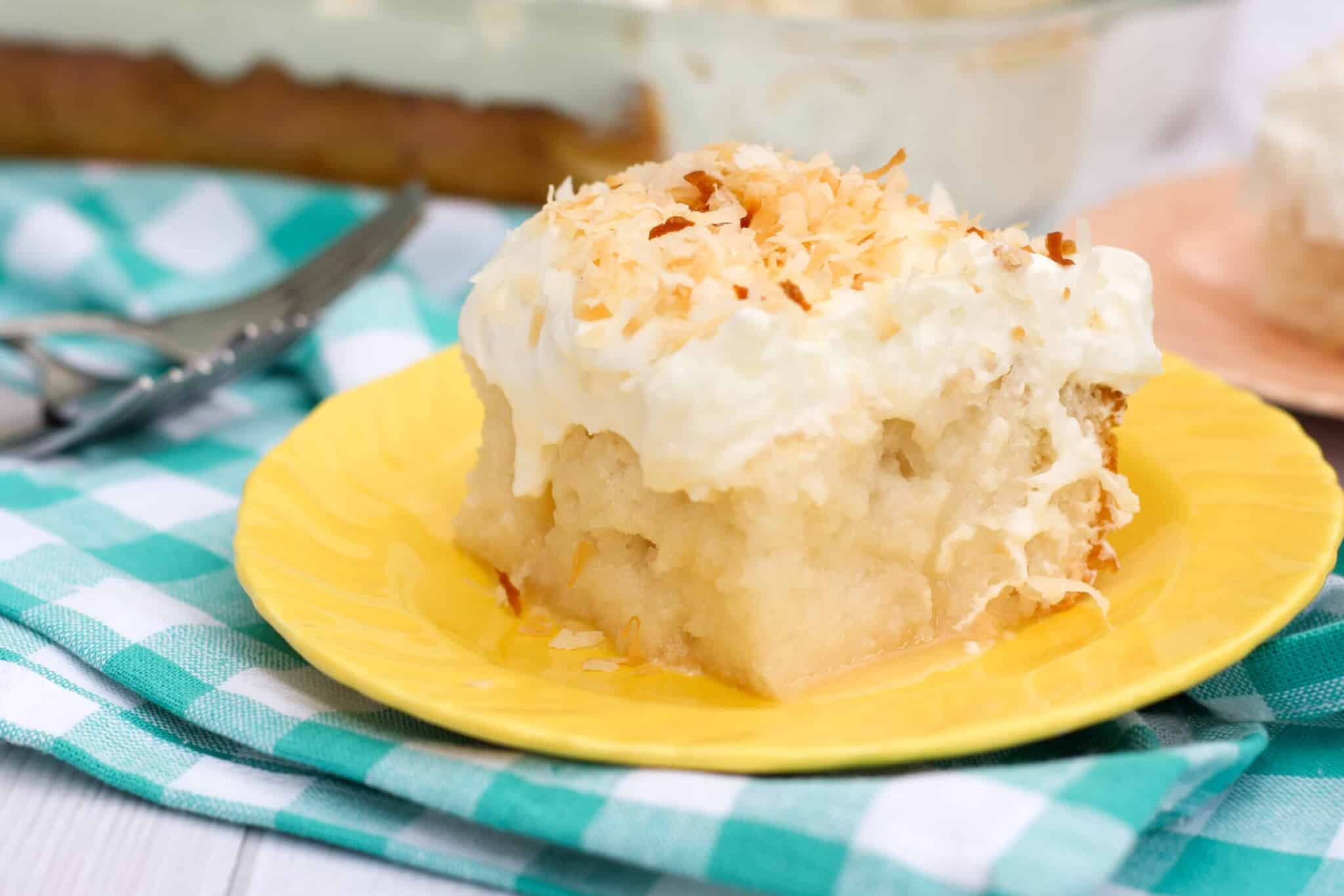 Gluten free coconut poke cake made with white cake, cream of coconut poured over the top, and topped with whipped cream and toasted coconut. So many layers of coconut flavor!
