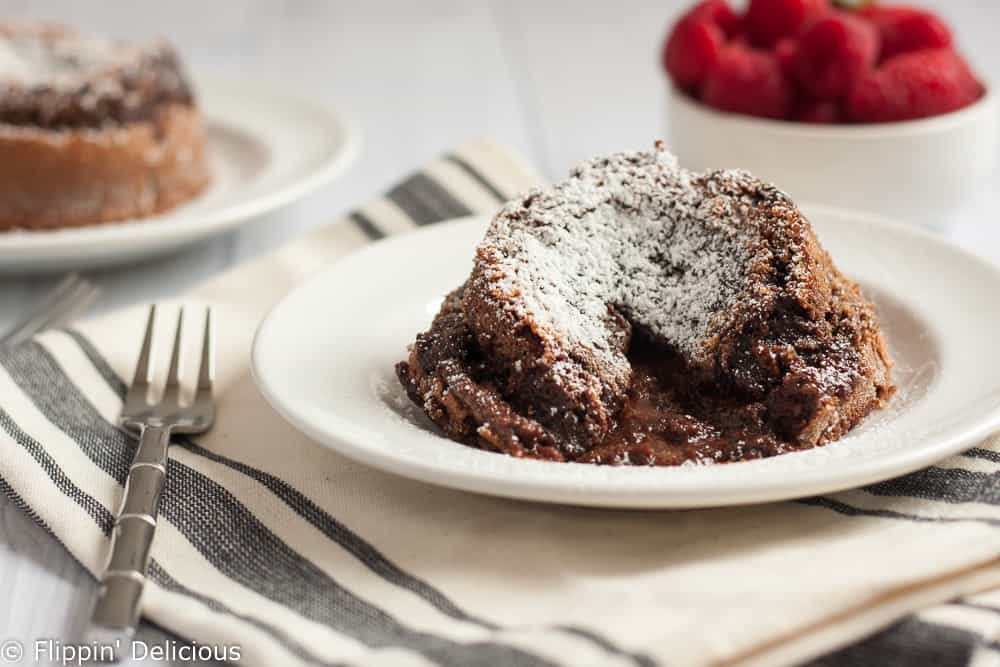 This decadent {Gluten Free} Flourless Molten Chocolate Lava Cake Recipe has just a few simple ingredients but the rich molten chocolate lava center will wow everyone. Perfect with a scoop of ice cream on top!