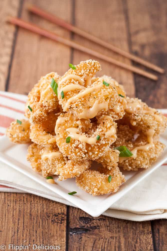 a pile of gluten free fried breaded shrimp drizzled in bang bang sauce, on a hite square plate, garnished ith green onions