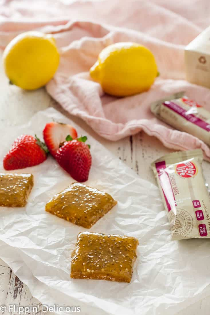 These no bake vegan gluten free lemon bars are a change of pace from the traditional. A chewy mixed berry flavored crust topped with a bright lemon curd with chia seeds make a fun no bake treat perfect for a warm day!