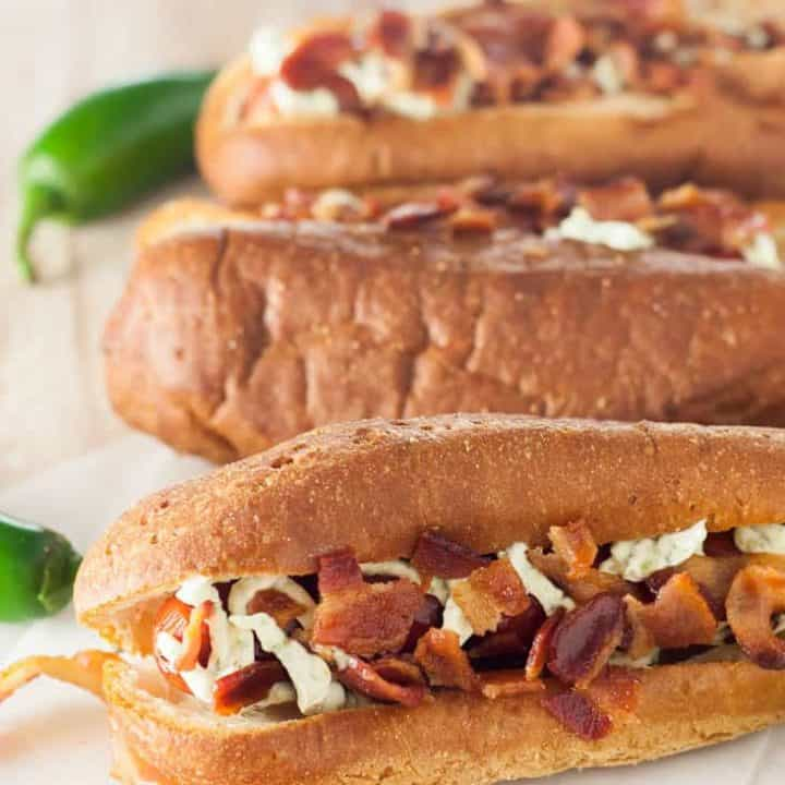 Gluten Free Jalapeno Popper Hot Dogs combine all of the flavors of your favorite spicy appetizer in a juicy grilled hot dog with bacon and a creamy jalapeno spread.