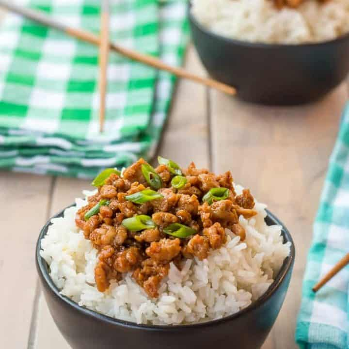 black matte bowl of rice topped with gluten free korean ground turkey garnished with green onions on a wooden table with another gluten free korean ground turkey and rice bowl in the background with teal and green napkins and wooden chopsticks
