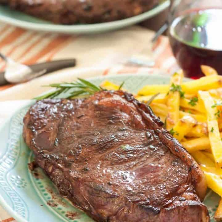 Juicy new york strip steaks marinated in red wine, rosemary, garlic and shallots with garlic and herb baked fries make a perfect at home date! Naturally gluten-free.