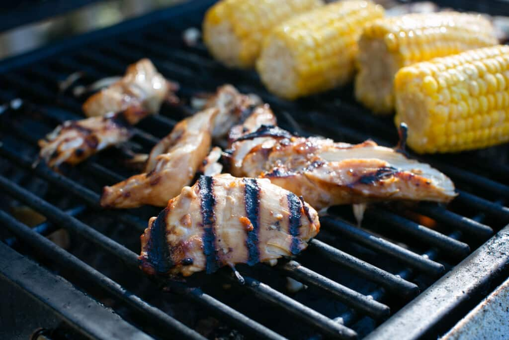 gluten free teriyaki chicken with grill marks on a grill with corn on the cob in the background