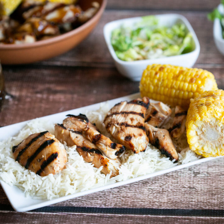 gluten free teriyaki chicken on a platter of rice with grilled corn on the cob