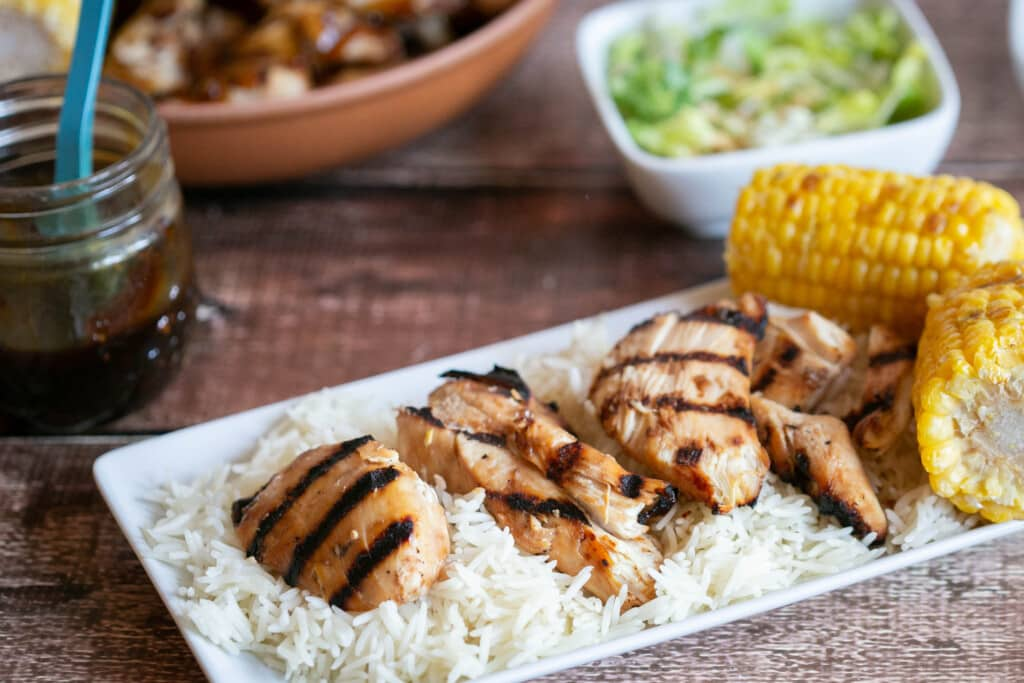 grilled gluten free teriyaki chicken on bed of rice on white plate with grilled corn on the cob