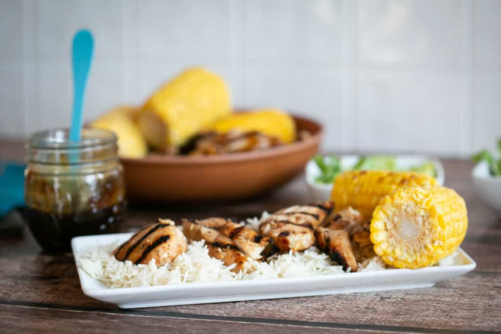 grilled gluten free teriyaki chicken on a white plate with rice and corn on a wooden table with homemade gluten free teriyaki sauce in a jar in the background
