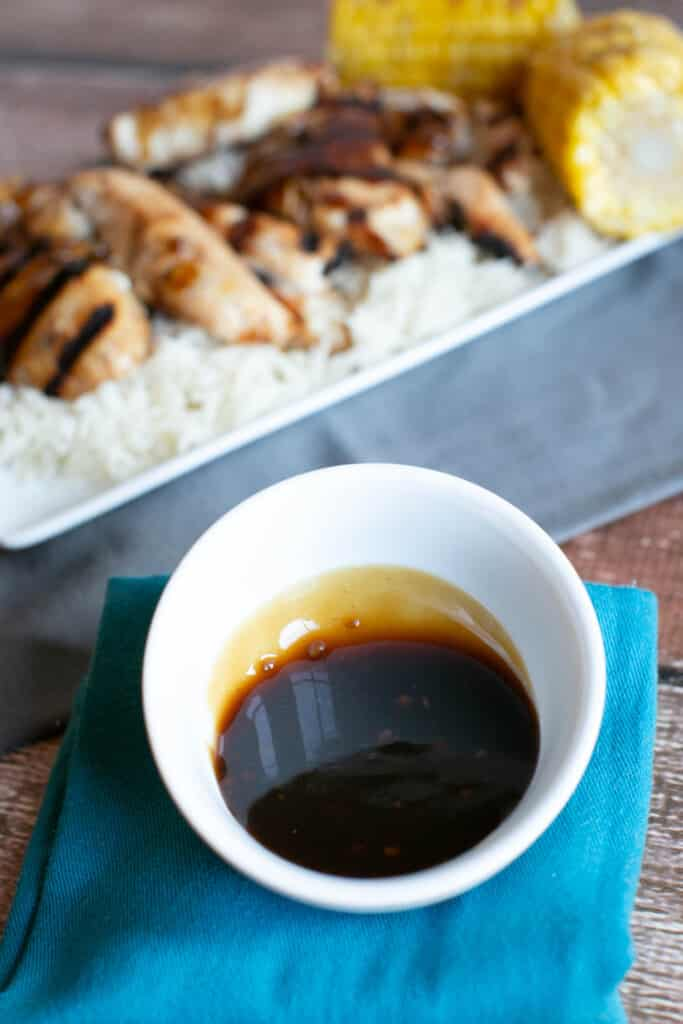 gluten free teriyaki sauce in a small white dish with gluten free grilled teriyaki chicken in the background on a bed of rice on a white platters