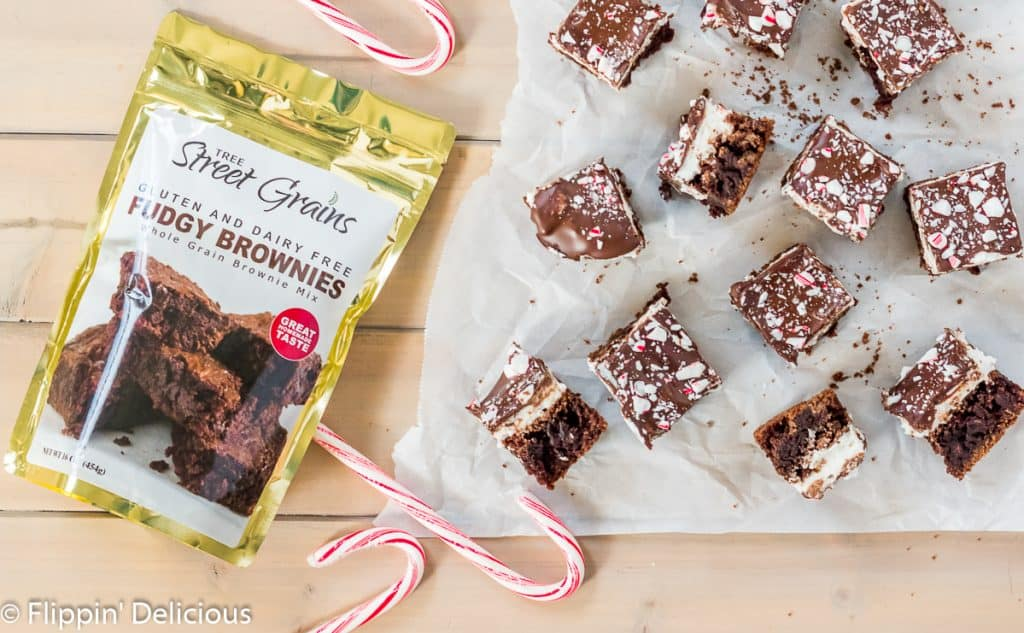 tree streat grains gluten and dairy free fudgy brownie mix on a wooden table beside candy canes and candy cane brownies on a piece of parchment paper