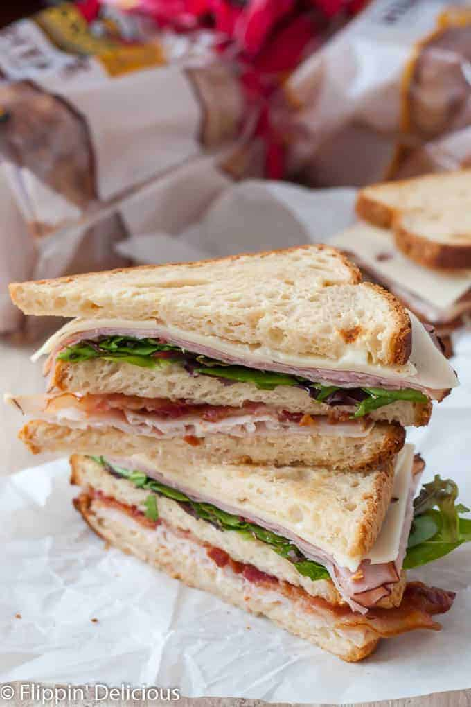 gluten free club sandwich with bacon, turkey, ham, canyon gluten free bread, cut in half on the diagonal and stack on top of each other