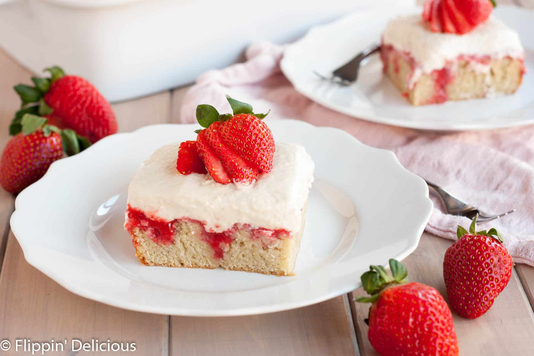 a slice of gluten free strawberry poke cake topped with a fresh strawberry on a white plate with scalloped edges on a light gray wooden table with fresh strawberries