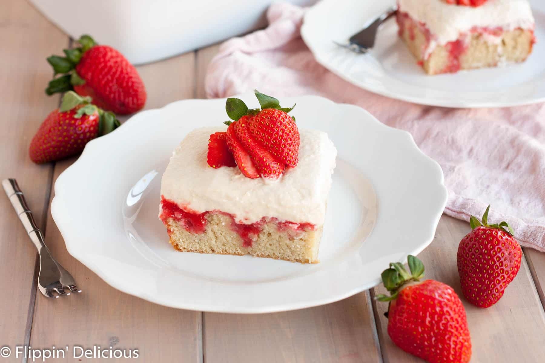 A slice of gluten free strawberry cake topped with fluffy pudding, strawberry sauce, and a fresh strawberry, sliced on top of a white plate on a light grey wood table with a small fork, fresh strawberries, and a light pink dish towel
