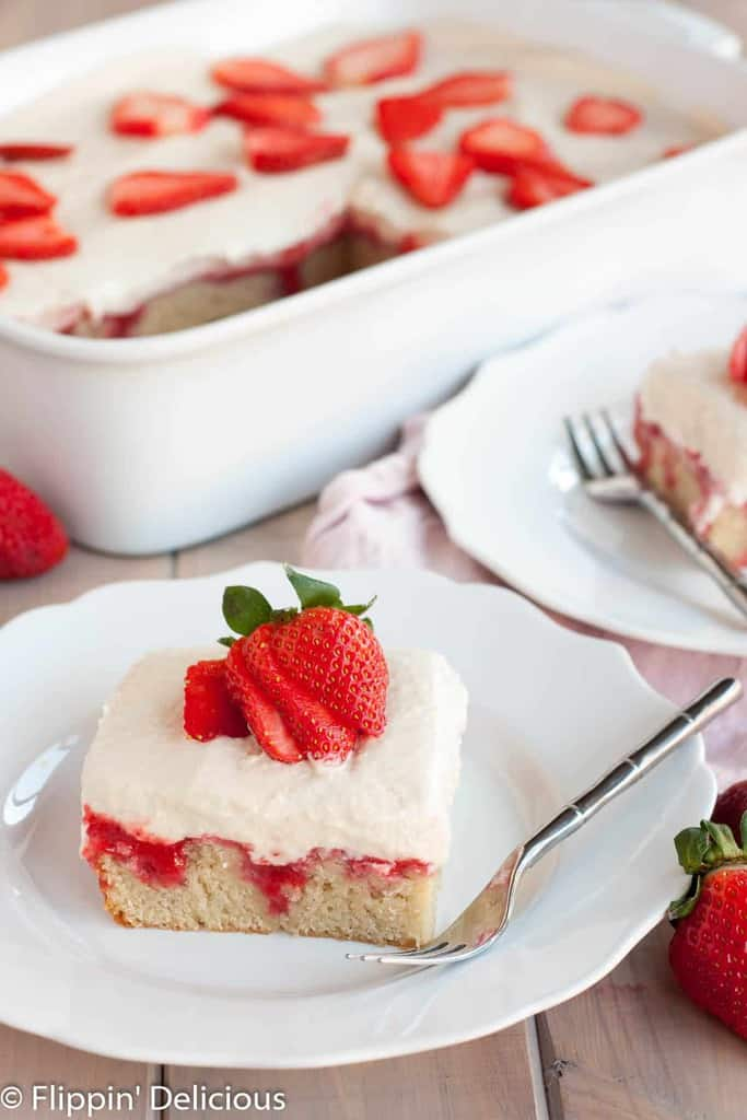 a slice of gluten free poke cake covered in homemade strawberry syrup and topped with a fluffy dairy free pudding and a sliced fresh strawberry, with a white pan with more gluten free strawberries and cream poke cake in the background