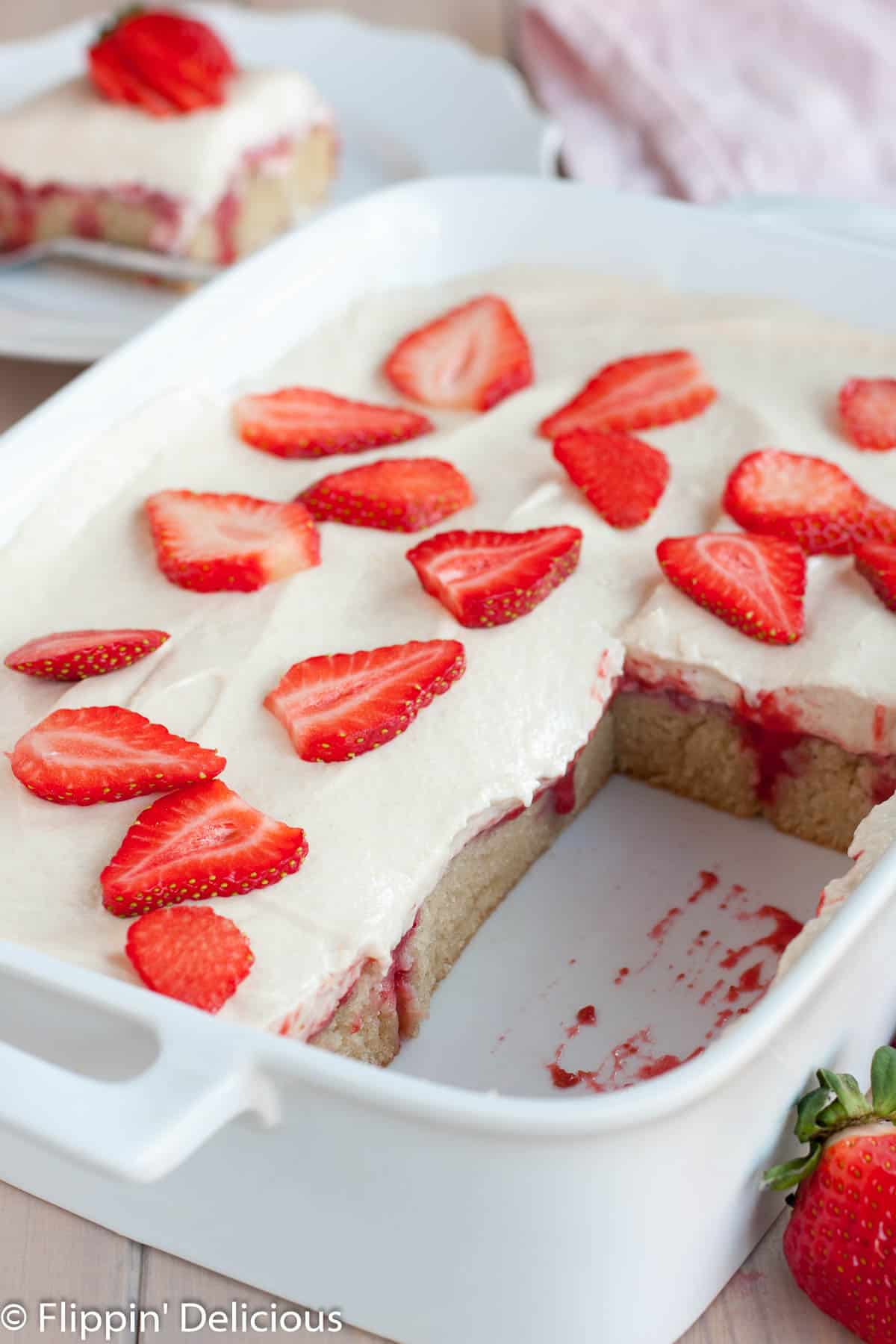 white ceramic rectangle pan filled with gluten free strawberries and cream poke cake , topped with sliced strawberries, with several slices removed