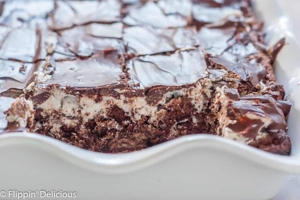 white baking pan with cut gluten free cookies and cream brownies inside, with oreo-style frosting and chocolate spread on top