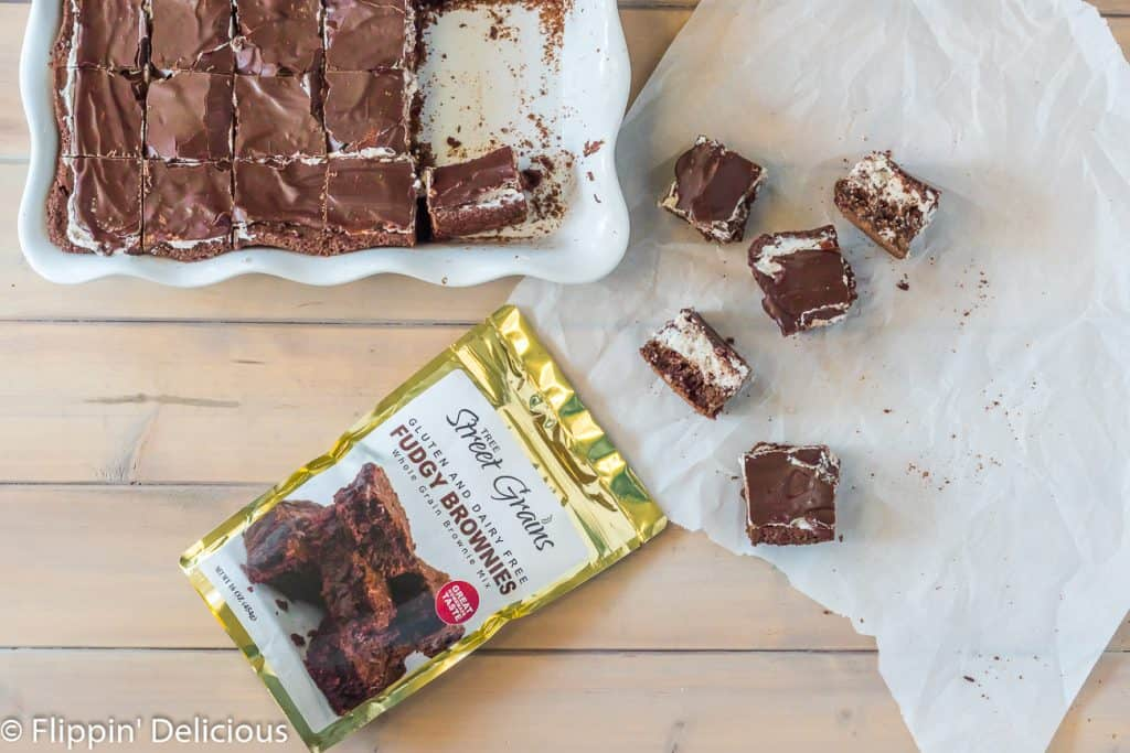 Overhead of Tree Street Grains Gluten and dairy free fudgy brownies mix beside baking pan of cookies and cream brownies, with a few brownies on a piece of parchment paper on the table.