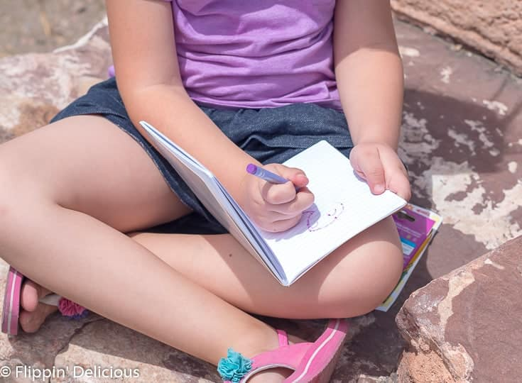 girl coloring sitting on a rock