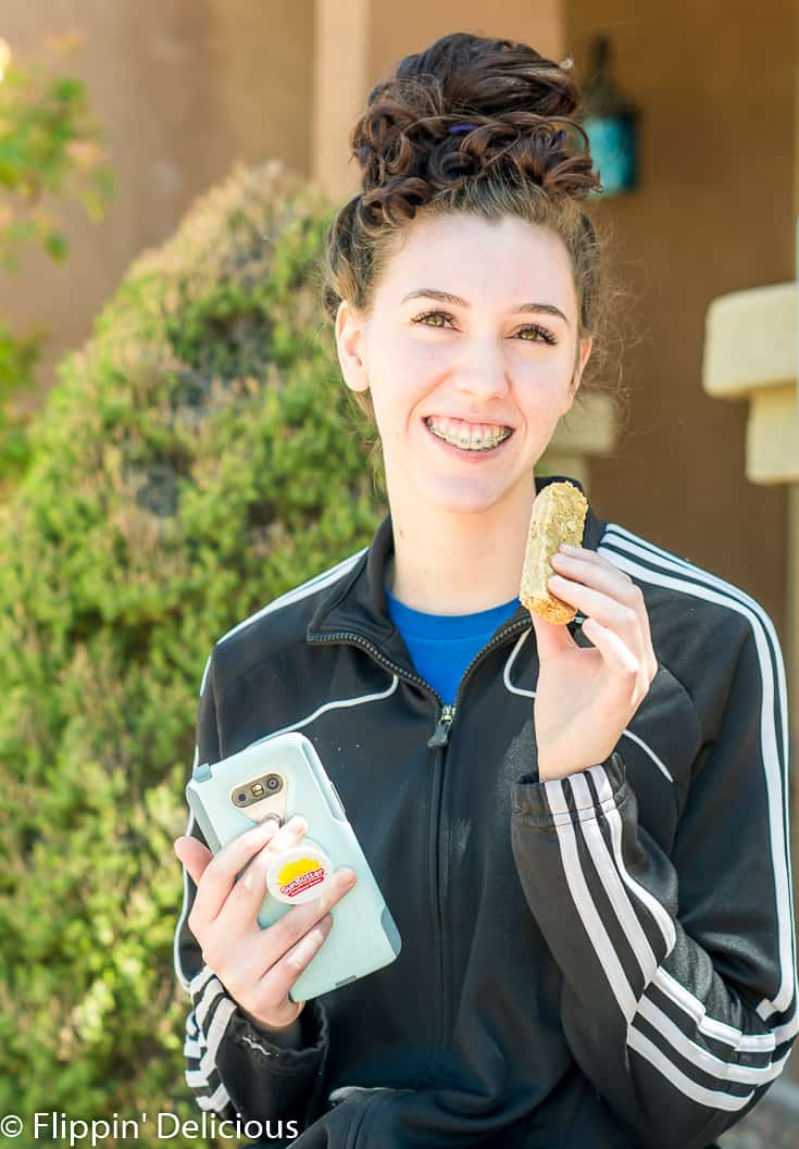 girl holding gluten free honey SunButter Granola Bar and cell phone with SunButter popsocket