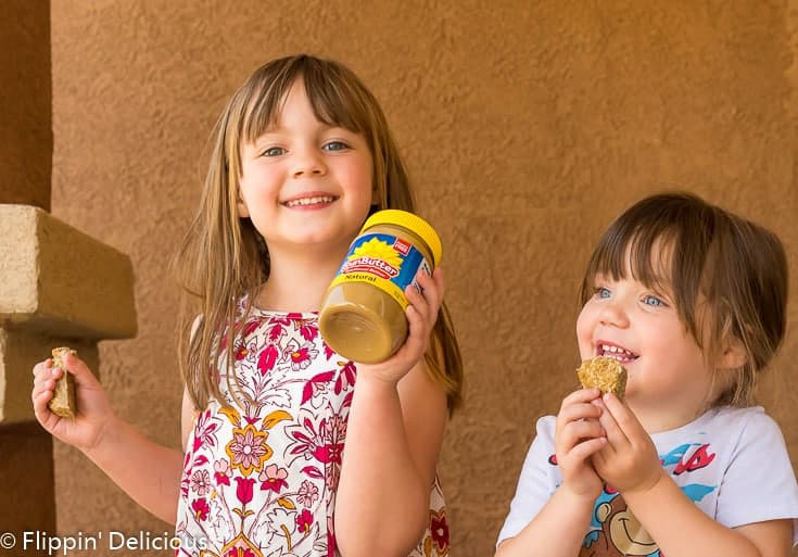 two young girls holding SunButter Sunflower Seed Butter and eating SunButter Honey Granola Bars