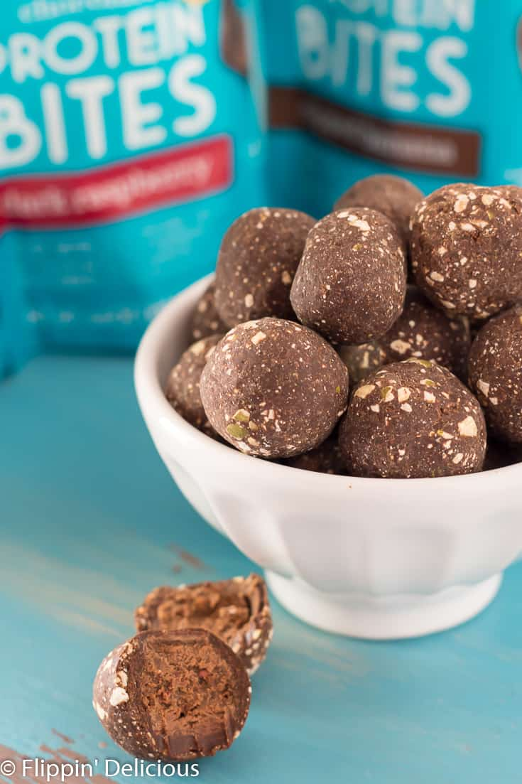 Bowl full of chocolate protein bites with half a dark raspberry chocolate protein bite and half of a dipped banana chocolate protein bite