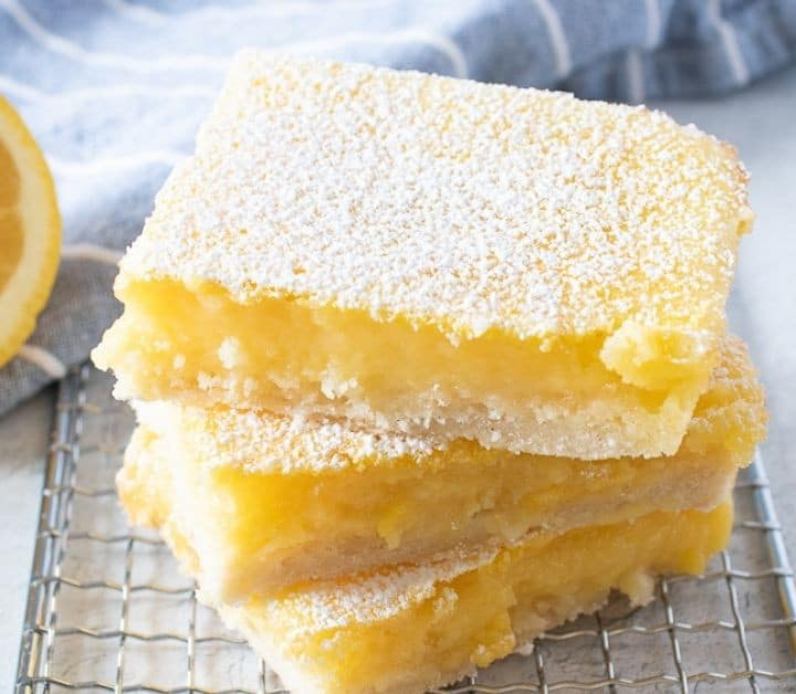 three gluten free lemon bars dusted with powdered sugar, stacked on top of each other on a wire cooling rack with a light blue striped dish towel in the background