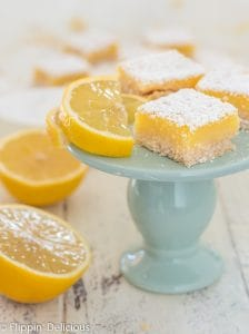 three gluten free lemon square bar cookies on small blue pedestal with lemon wedge and lemon cut in half