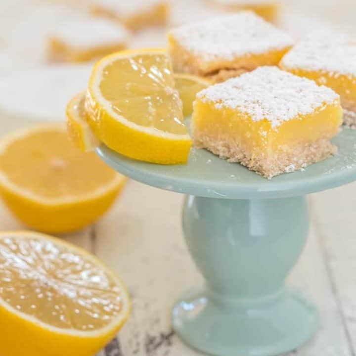 three gluten free lemon square bar cookies on small blue pedestal with lemon wedge and lemon cut in half