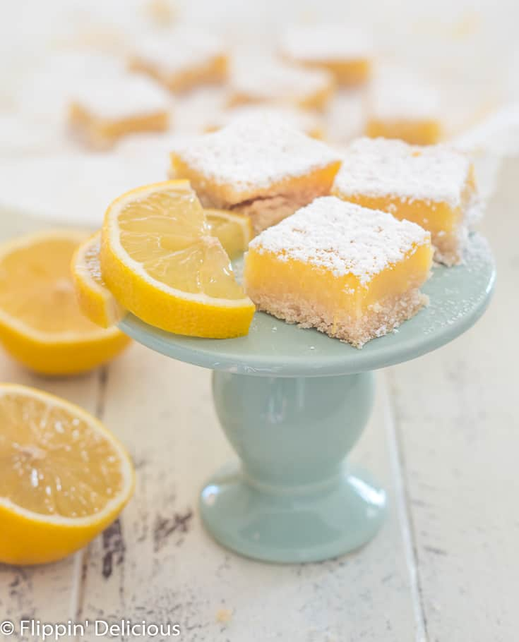 three gluten free lemon bars sprinkled with powdered sugar next to lemon slice on blue plate