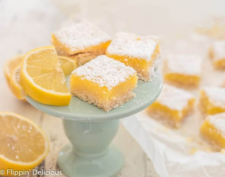 three gluten free lemon squares on blue plate next to lemon slice. More lemon squares and a lemon cut in half in the background