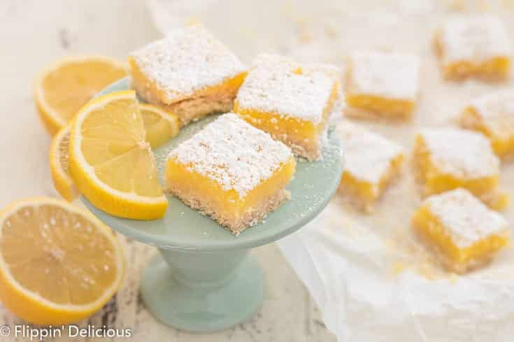 three gluten free lemon bars on a small blue pedestal next to lemon wedge