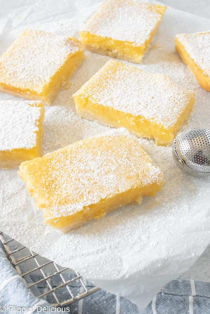 gluten free lemon squares on a white napkin, all sprinkled with powdered sugar