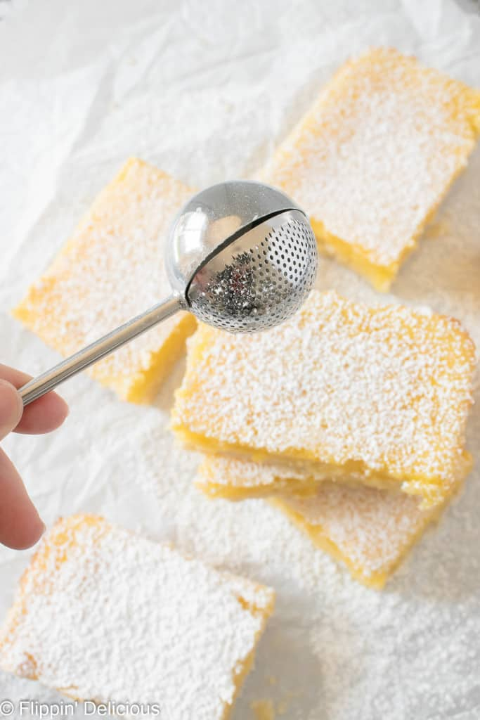 powdered sugar duster sprinkling powdered sugar over a stack of gluten free lemon bars