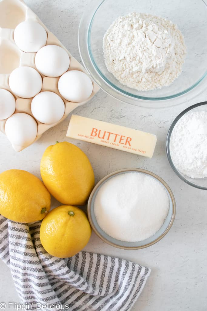 ingredients for gluten free lemon bars on a white table, whole lemons, eggs, a stick of butter, granulated sugar, powdered sugar, ad gluten free flour with a light blue striped dishtowel