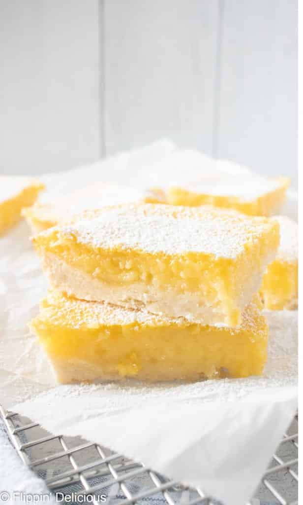 two gluten free lemon bars stacked on top of eachother on a white napkin with more lemon squares in the background