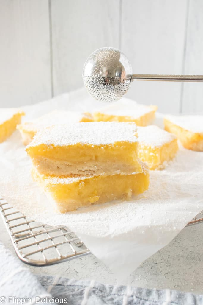 metal powdered sugar duster ball sprinkling powdered sugar over two gluten free lemon squares on a white napkin on a metal cooling rack