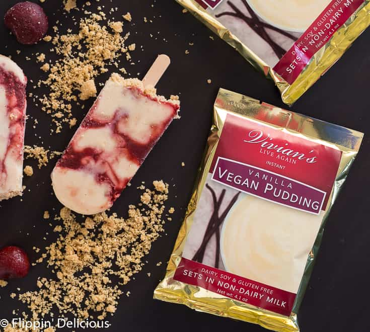 vegan cheesecake pudding pop swirled with cherries and gluten free graham-style crumbs on dark table with packet of Vivian's Live Again Vegan Instant Pudding