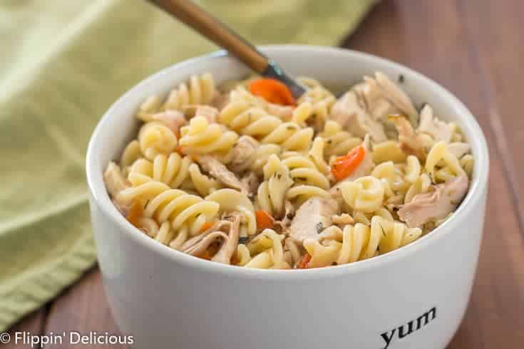 Instant Pot gluten free chicken noodle soup with carrots and rotisserie chicken in white bowl with wooden handle spoon