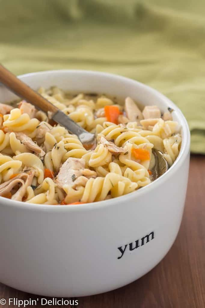 Instant Pot gluten free chicken noodle soup in white bowl with wood handle spoon